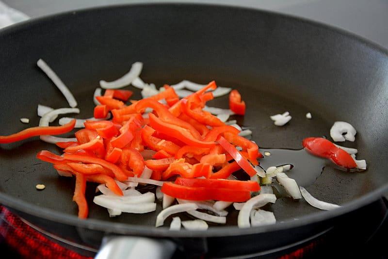 Für die Avocado-Bohnen-Quesadillas werden Zwiebel und Paprika angedünstet