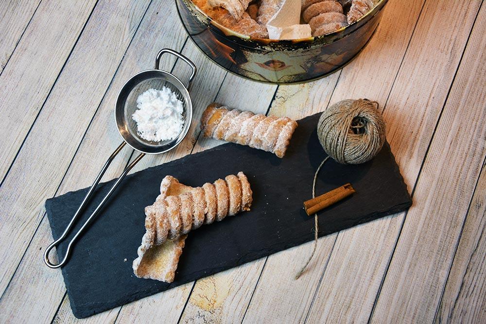 Original steirische Spagatkrapfen kann man mit einer Spagatkrapfenzange machen oder man bindet den Teig einfach mit einem Spagat an ein Rundholz.